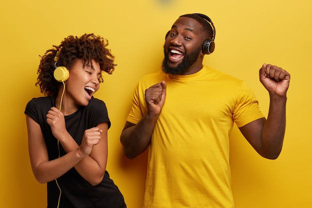 Jonge man en vrouw luisteren naar muziek in de koptelefoon Gratis Foto