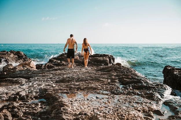 Jonge man en vrouw met surfplanken die op steenkust gaan aan water Gratis Foto