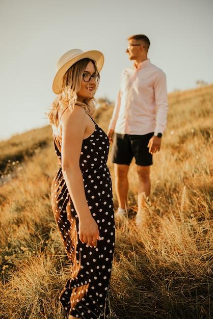 Jonge man en vrouw wandelen in de wei bij zonsondergang in de zomer in de buurt van het meer. Premium Foto