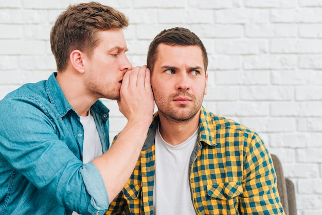 Jonge man fluisteren een geheim in het oor van zijn vriend Gratis Foto