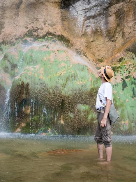 Jonge man genieten in natuurpark aan de voet van grote waterval Premium Foto