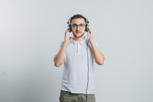 Jonge man genieten van muziek met koptelefoon in wit t-shirt, broek en op zoek zelfverzekerd Gratis Foto