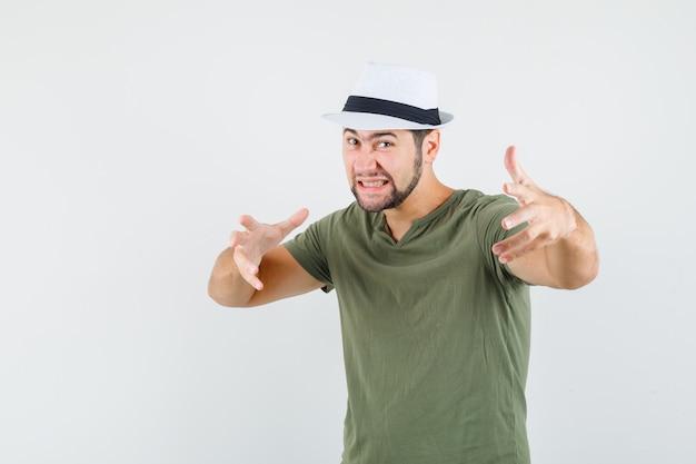 Jonge man handen uitrekken zoals iets in groen t-shirt en hoed grijpen en agressief kijken Gratis Foto