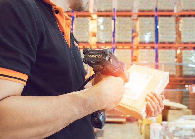Jonge man houden barcodescanner met scannen op een pakket box. Premium Foto