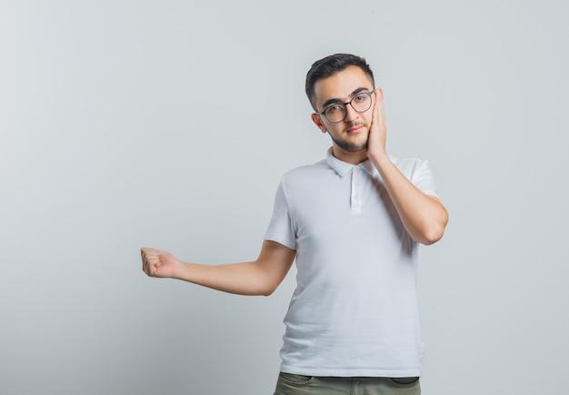 Jonge man houdt de hand op de wang, wijst weg in wit t-shirt, broek en kijkt verstandig Gratis Foto