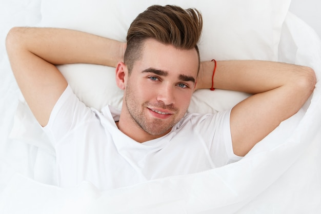 Jonge man in bed Gratis Foto