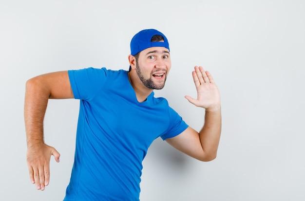 Jonge man in blauw t-shirt en pet gebaren als beweging maken en er grappig uitzien Gratis Foto