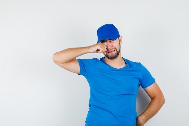 Jonge man in blauw t-shirt en pet huilen als een kind en depressief kijken Gratis Foto