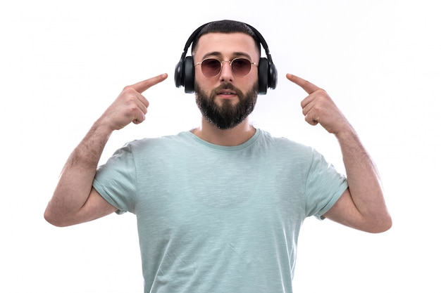 Jonge man in blauw t-shirt met baard luisteren naar muziek via zwarte hoofdtelefoon Gratis Foto