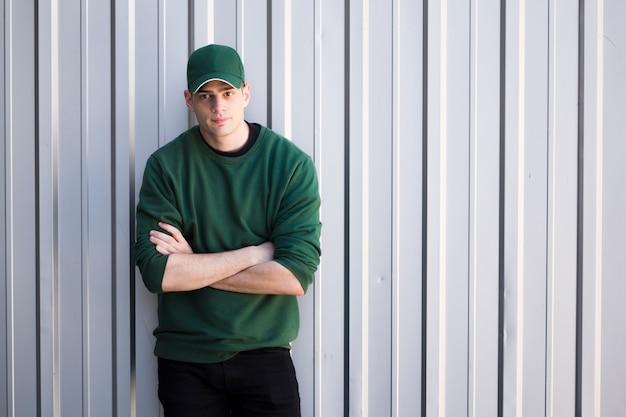 Jonge man in cap met gekruiste armen permanent tegen grijze muur Gratis Foto