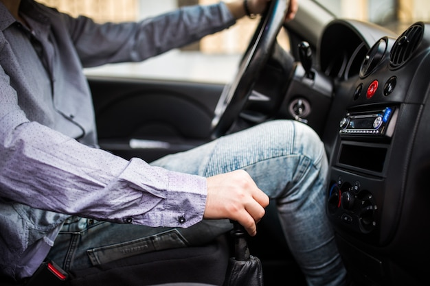 Jonge man in de auto schakelt versnelling Gratis Foto