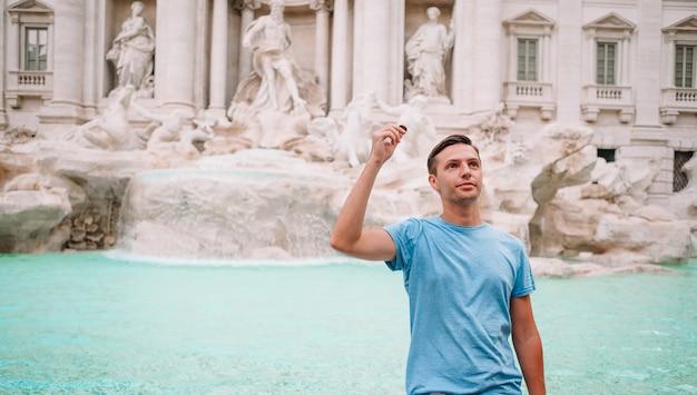 Jonge man in de buurt van fontein fontana di trevi met munten in handen Premium Foto