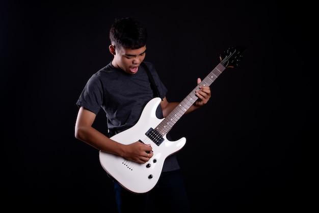 Jonge man in een donker t-shirt met elektrische gitaar Gratis Foto