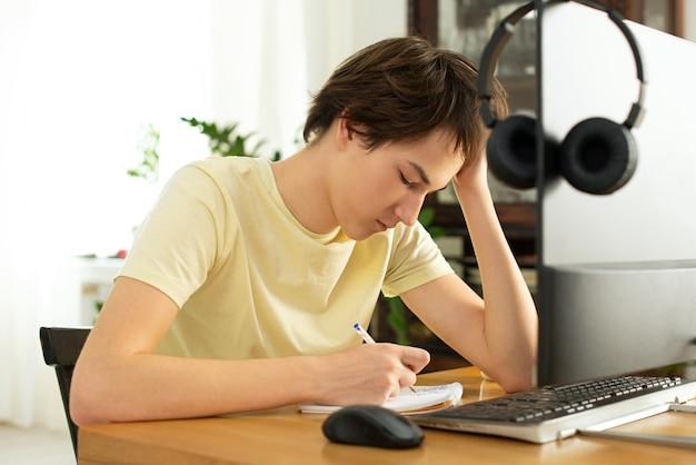 Jonge man in een geel t-shirt werkt thuis op de computer. online chatten. werken op afstand via internet op isolatie Premium Foto