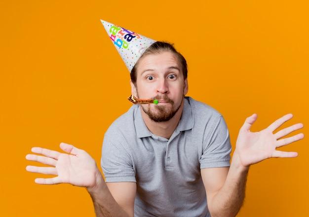Jonge man in feestmuts blaast een wistle blij en verrast spreidende armen naar de zijkanten verjaardagsfeestje concept staande over oranje muur Gratis Foto