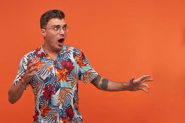 Jonge man in gebloemd overhemd met wijd geopende mond staande over de oranje achtergrond, handen opsteken, wegkijken, bril dragen, bang kijken Gratis Foto