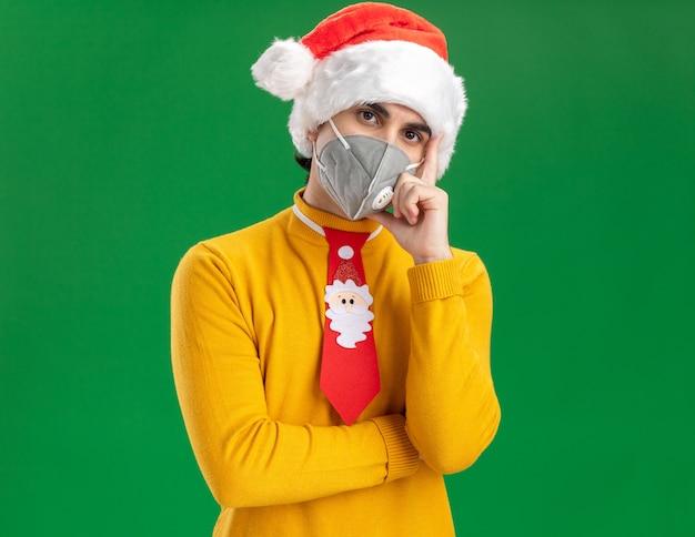 Jonge man in gele coltrui en kerstmuts met grappige stropdas dragen beschermend gezichtsmasker camera kijken met ernstig gezicht met hand op kin denken staande over groene achtergrond Gratis Foto