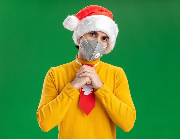 Jonge man in gele coltrui en kerstmuts met grappige stropdas dragen gezicht beschermend masker kijken camera hand in hand samen staande over groene achtergrond Gratis Foto