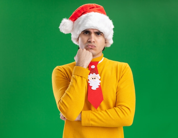 Jonge man in gele coltrui en kerstmuts met grappige stropdas kijken camera ontevreden met hand op zijn kin staande over groene achtergrond Gratis Foto