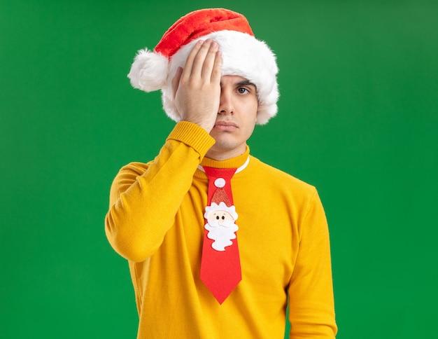 Jonge man in gele coltrui en kerstmuts met grappige stropdas kijken camera wirth ernstig gezicht bedekt één oog met hand staande over groene achtergrond Gratis Foto
