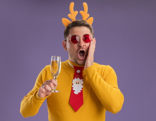Jonge man in gele coltrui en rode bril dragen grappige rode stropdas en rand met herten hoorns houden glas champagne kijken camera verbaasd en verrassend staande over paarse achtergrond Gratis Foto