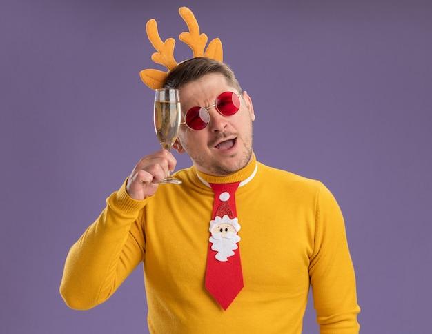 Jonge man in gele coltrui en rode bril dragen grappige rode stropdas en rand met herten hoorns kijken camera blij en positief houden glas champagne staande over paarse achtergrond Gratis Foto