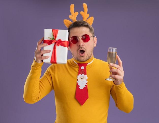 Jonge man in gele coltrui en rode bril met grappige rode stropdas en rand met herten hoorns met glas champagne en heden kijkt verbaasd en verbaasd staande over paarse achtergrond Gratis Foto