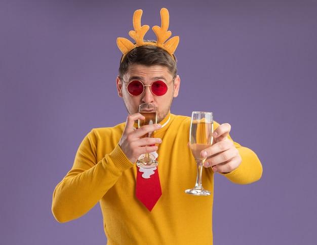 Jonge man in gele coltrui en rode bril met grappige rode stropdas en rand met herten hoorns met twee glazen champagne blij en positief staande over paarse achtergrond Gratis Foto