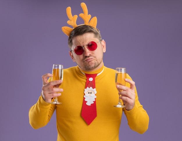 Jonge man in gele coltrui en rode bril met grappige rode stropdas en rand met herten hoorns met twee glazen champagne op zoek verward en ontevreden staande over paarse achtergrond Gratis Foto