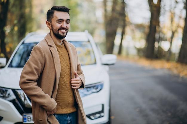 Jonge man in het bos dragen jas door de auto Gratis Foto