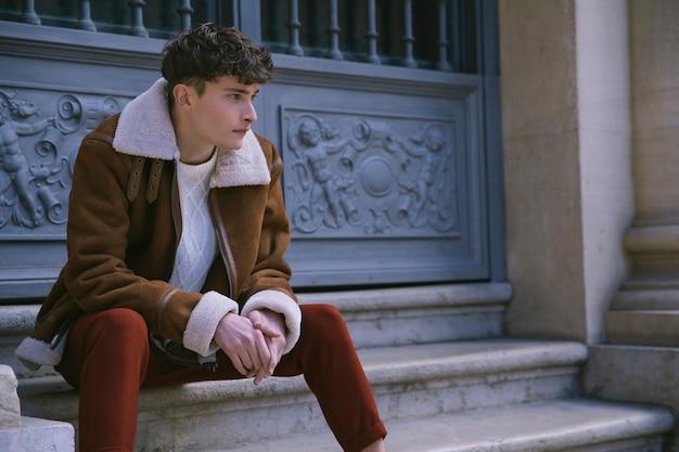 Jonge man in jas zit bij de voordeur Gratis Foto