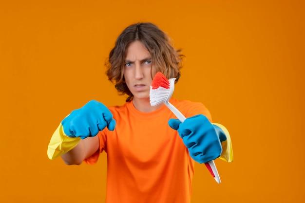 Jonge man in oranje t-shirt dragen rubberen handschoenen met schrobborstel balde vuist naar camera met boze uitdrukking staande over gele achtergrond Gratis Foto