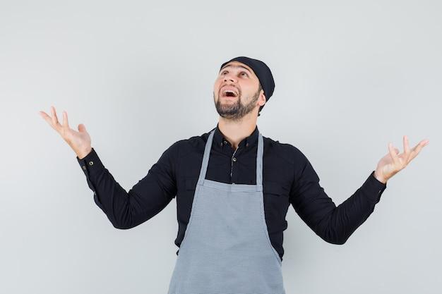 Jonge man in overhemd, schort die handen opheft terwijl hij omhoog kijkt en dankbaar kijkt, vooraanzicht. Gratis Foto