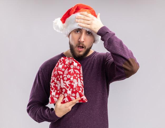 Jonge man in paarse trui en kerstmuts met rode tas met geschenken op zoek verward met de hand op zijn hoofd, vergat staande op witte achtergrond Gratis Foto