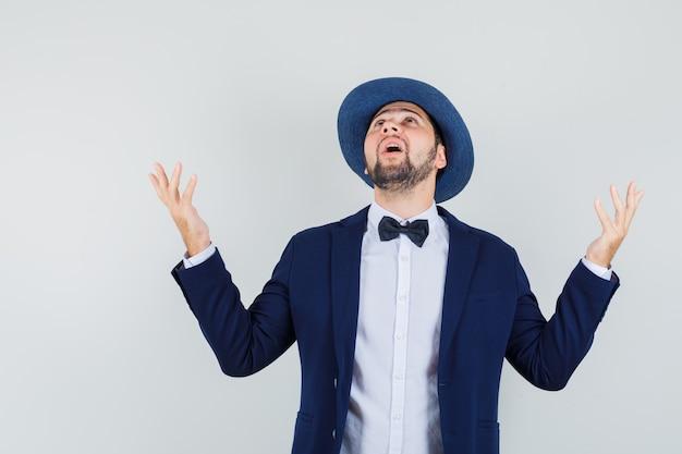 Jonge man in pak, hoed die handen opheft terwijl hij omhoog kijkt en dankbaar kijkt, vooraanzicht. Gratis Foto