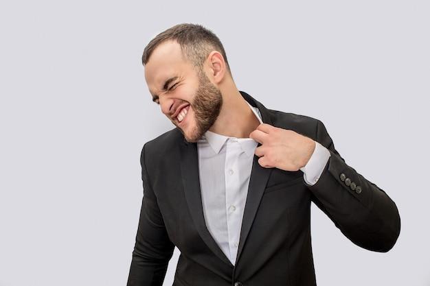 Jonge man in pak lijdt. hij houdt de rand van de kraag vast en trek eraan. jonge man krimpt. Premium Foto