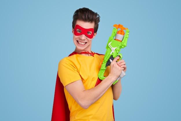 Jonge man in superheld masker en cape glimlachend voor camera en trekker op speelgoed wapen trekken tegen blauwe achtergrond Premium Foto