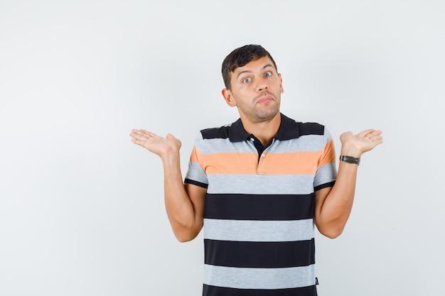 Jonge man in t-shirt die palmen opheft alsof hij iets vasthoudt en er verward uitziet Gratis Foto