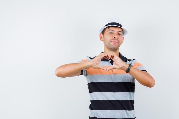 Jonge man in t-shirt en hoed die hartgebaar toont en vrolijk kijkt Gratis Foto
