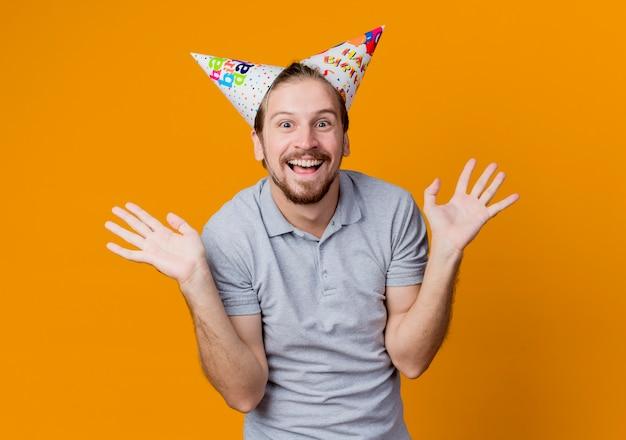 Jonge man in vakantie caps glimlachend blij en opgewonden concept van de verjaardagspartij staande over oranje muur Gratis Foto