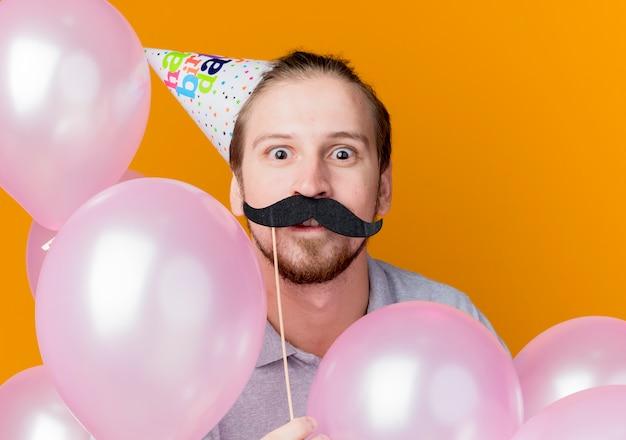 Jonge man in vakantie glb bedrijf snor partij stok verrast verjaardagsfeestje concept staande met lucht ballonnen over oranje muur Gratis Foto