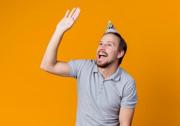 Jonge man in vakantie glb opzij zwaaien met hand glimlachend vrolijk verjaardagsfeestje concept staande over oranje muur Gratis Foto