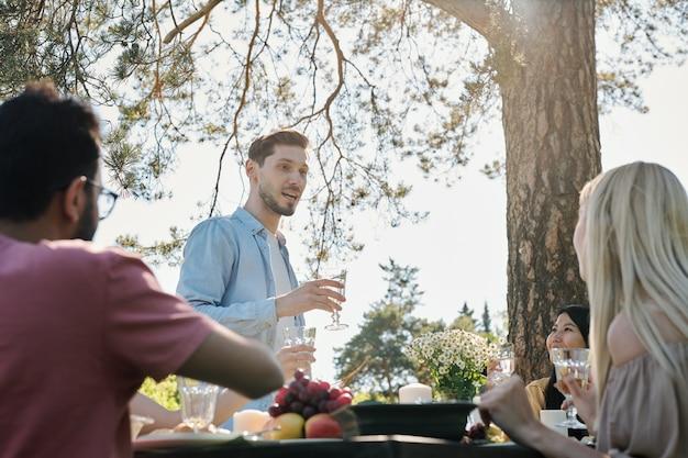 Jonge man in vrijetijdskleding toast uitspreken terwijl hij stond door geserveerd tafel voor zijn vrienden tijdens het diner onder dennenboom buitenshuis Premium Foto