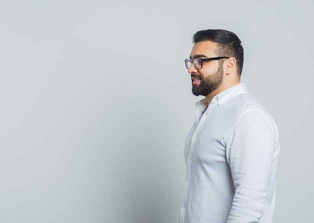 Jonge man in wit overhemd kijken naar de voorkant oh hem en peinzend kijken. Gratis Foto