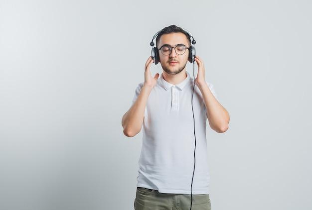 Jonge man in wit t-shirt, broek genieten van muziek met koptelefoon en op zoek ontspannen Gratis Foto