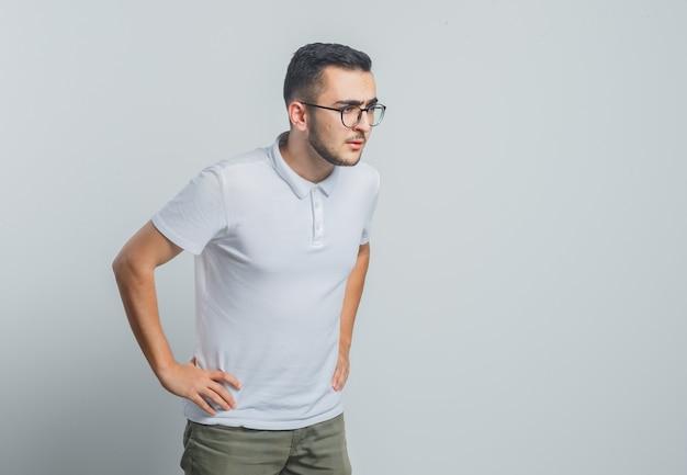 Jonge man in wit t-shirt, broek wegkijken met handen op taille en op zoek gericht Gratis Foto