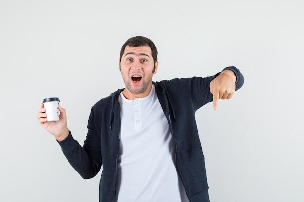 Jonge man in wit t-shirt en zwarte hoodie met ritssluiting die afhaalmaaltijden koffiekopje houdt en met wijsvinger naar beneden wijst en verbaasd, vooraanzicht kijkt. Gratis Foto