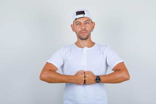 Jonge man in wit t-shirt, pet stoot zijn vuisten en kijkt zelfverzekerd, vooraanzicht. Gratis Foto