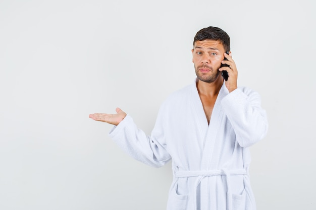 Jonge man in witte badjas praten over de telefoon met hulpeloos gebaar opzij, vooraanzicht. Gratis Foto