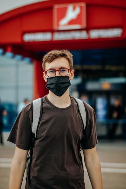 Jonge man in zwart t-shirt, chirurgisch masker, bril, rugzak kijken naar de camera. luchthaven op de achtergrond Premium Foto